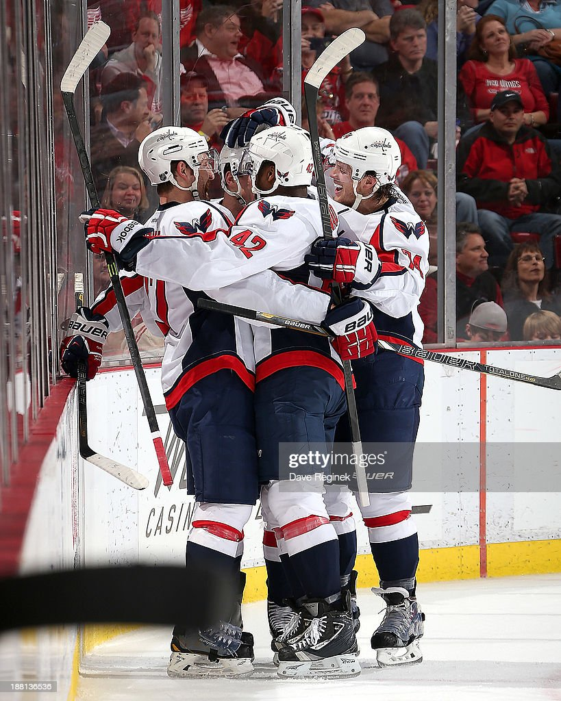 Alex Ovechkin #8, Joel Ward #42 and John Carlson #74 of the Washington Capitals surround teammate Michael Latta #46 after scoring a goal during an NHL game against the Detroit Red Wings at Joe Louis Arena on November 15, 2013 in Detroit, Michigan.