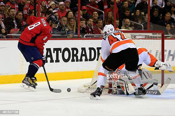 Alex Ovechkin of the Washington Capitals and Andrew MacDonald of the Philadelphia Flyers go after the puck during the third period of the Capitals...