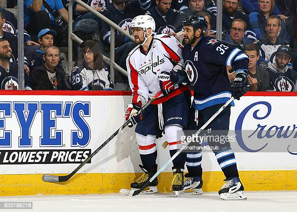 Alex Ovechkin of the Washington Capitals and Dustin Byfuglien of the Winnipeg Jets keep an eye on the play as they battle along the boards during...