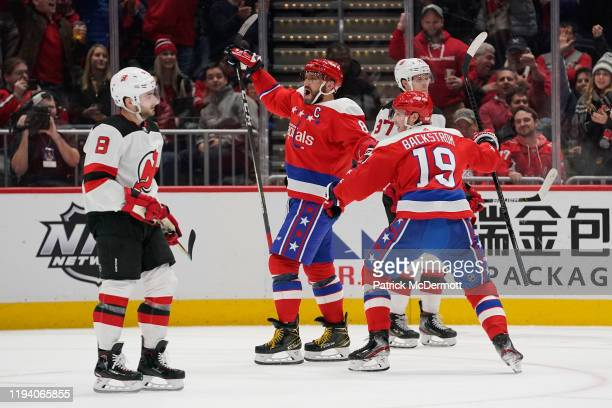 Alex Ovechkin of the Washington Capitals celebrates with teammate Nicklas Backstrom after scoring his third goal of the game for a hat trick against...