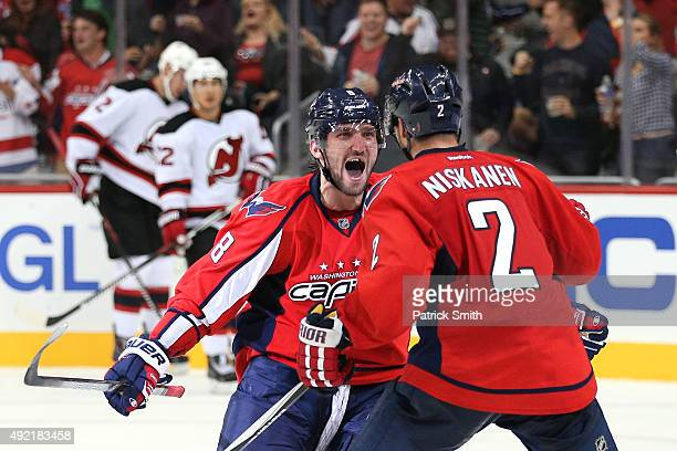 Alex Ovechkin of the Washington Capitals celebrates with teammate Matt Niskanen after scoring a third period goal against the New Jersey Devils at...
