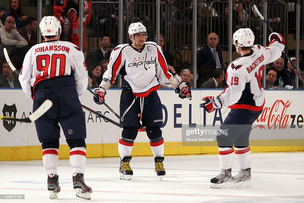 Alex Ovechkin #8 of the Washington Capitals celebrates with teammates Marcus Johansson #90 and Nicklas Backstrom #19 after Ovechkin scored a goal to give the Capitals a 3-2 lead in the third period in Game Two of the Eastern Conference Semifinals during the 2012 NHL Stanley Cup Playoffs at Madison Square Garden on April 30, 2012 in New York City.
