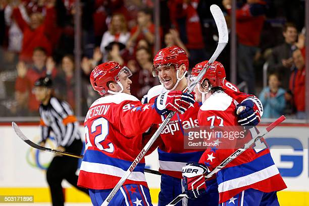 Alex Ovechkin of the Washington Capitals celebrates with teammates after scoring an empty net goal against the Buffalo Sabres during the third period...