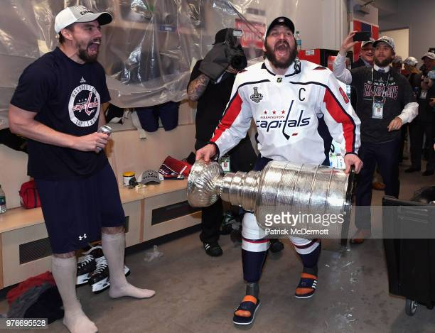 Alex Ovechkin of the Washington Capitals celebrates with the Stanley Cup as he walks into the locker room after his team defeated the Vegas Golden...
