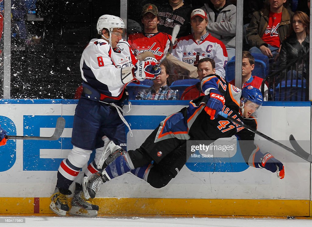 Alex Ovechkin #8 of the Washington Capitals checks Andrew MacDonald #47 of the New York Islanders at Nassau Veterans Memorial Coliseum on March 9, 2013 in Uniondale, New York. The Islanders defeated the Capitals 5-2.