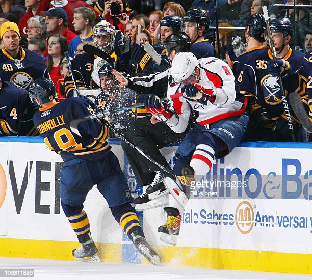Alex Ovechkin of the Washington Capitals crashes into the Buffalo Sabres bench alongside linesman Steve Barton trying to avoid Tim Connelly of the...