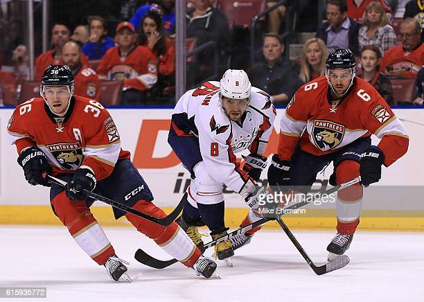 Alex Ovechkin of the Washington Capitals fights for the puck with Jussi Jokinen and Alex Petrovic of the Florida Panthers during a game at BBT Center...