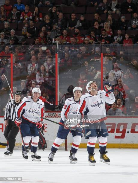 Alex Ovechkin of the Washington Capitals flips a game puck with which teammate Tyler Lewington scored his first career NHL goal in the air during the...