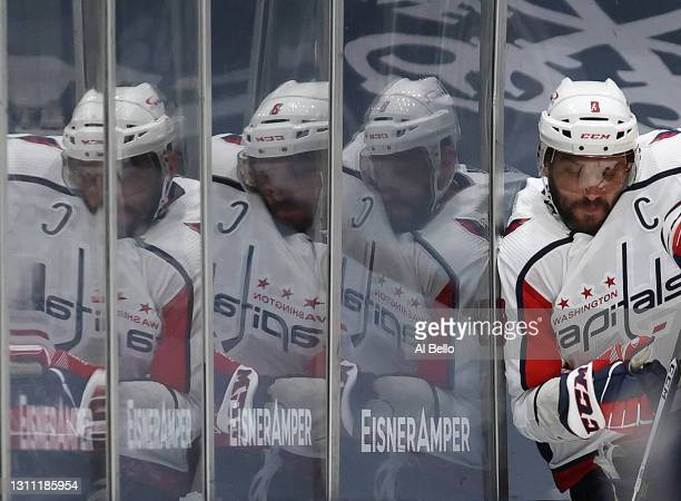 Alex Ovechkin of the Washington Capitals is checked against the against the New York Islanders during their game at Nassau Coliseum on April 06, 2021...