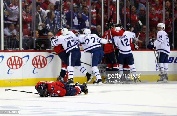 Alex Ovechkin of the Washington Capitals lays on the ice after being injured as members of the Capitals and Toronto Maple Leafs scuffle in the first...