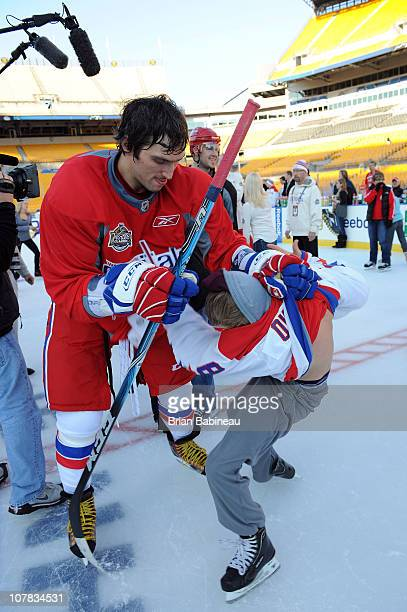 Alex Ovechkin of the Washington Capitals play fights with a kid during a family skate following practice for the 2011 NHL Bridgestone Winter Classic...