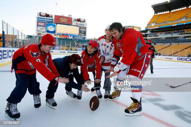 Alex Ovechkin of the Washington Capitals plays with a football wit some kids on the ice during a family skate following practice for the 2011 NHL...