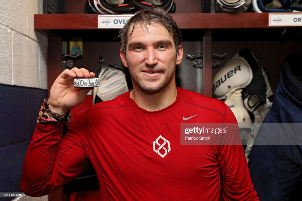 Alex Ovechkin #8 of the Washington Capitals poses with the puck commemorating his 600th career goal in which he scored during the second period against the Winnipeg Jets at Capital One Arena on March 12, 2018 in Washington, DC.