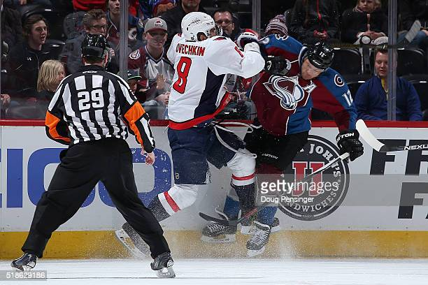 Alex Ovechkin of the Washington Capitals puts a hit on Jarome Iginla of the Colorado Avalanche as referee Ian Walsh oversees the action at Pepsi...
