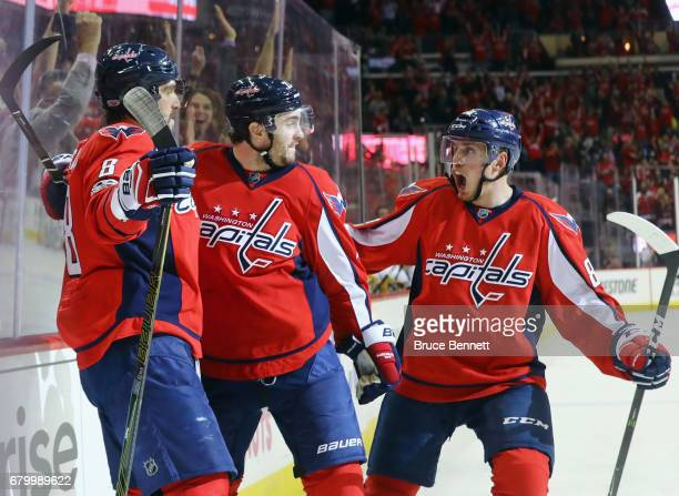 Alex Ovechkin of the Washington Capitals scores at 7:47 of the third period against the Pittsburgh Penguins and is embraced by Kevin Shattenkirk and...