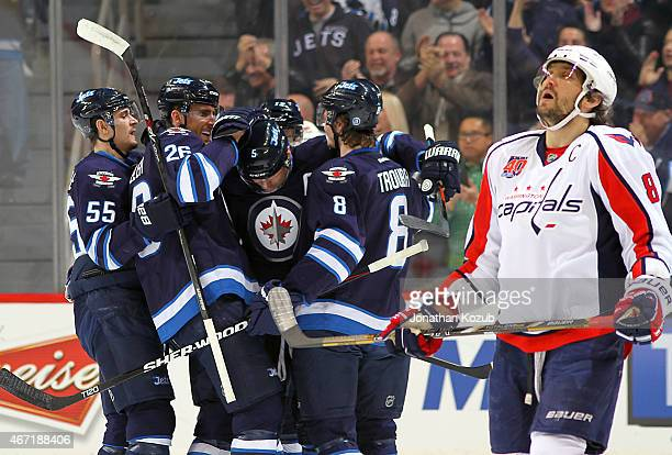 Alex Ovechkin of the Washington Capitals skates away as members of the Winnipeg Jets celebrates a first period goal by Mark Stuart on March 21 2015...