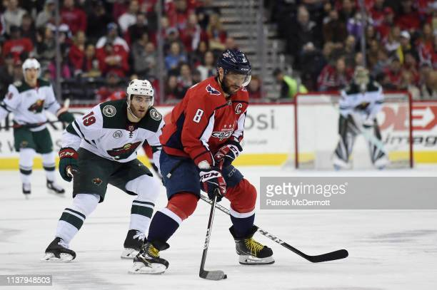 Alex Ovechkin of the Washington Capitals skates with the puck against Luke Kunin of the Minnesota Wild in the second period at Capital One Arena on...