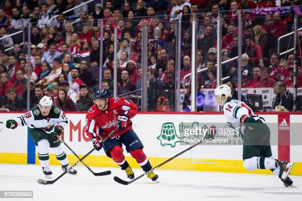 Alex Ovechkin of the Washington Capitals skates with the puck against Luke Kunin and Joel Eriksson Ek of the Minnesota Wild in the third period at...