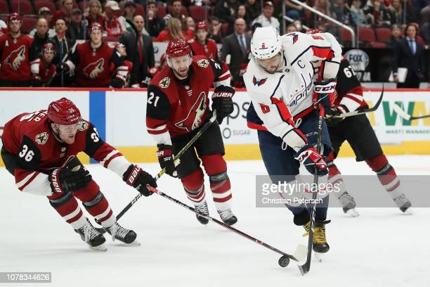 Alex Ovechkin of the Washington Capitals skates with the puck ahead of Christian Fischer and Derek Stepan of the Arizona Coyotes during the third...