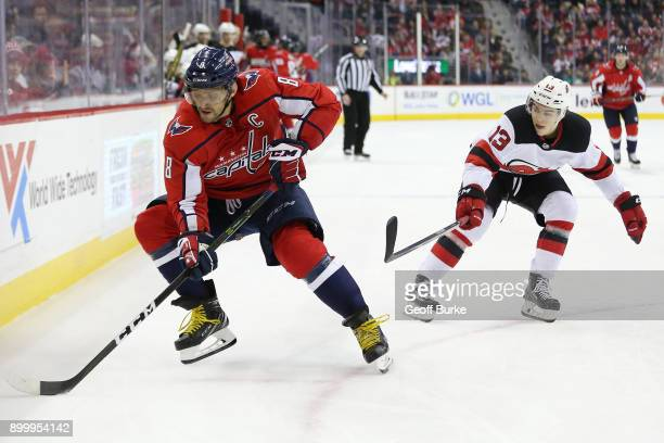 Alex Ovechkin of the Washington Capitals skates with the puck as Nico Hischier of the New Jersey Devils chases at Capital One Arena on December 30...
