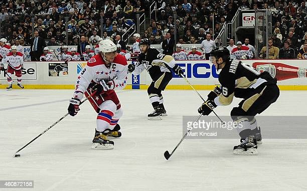 Alex Ovechkin of the Washington Capitals skates with the puck as Scott Harrington of the Pittsburgh Penguins tries to defend at Consol Energy Center...