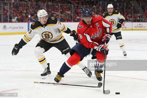 Alex Ovechkin of the Washington Capitals skates with the puck past Charlie McAvoy of the Boston Bruins during the second period at Capital One Arena...