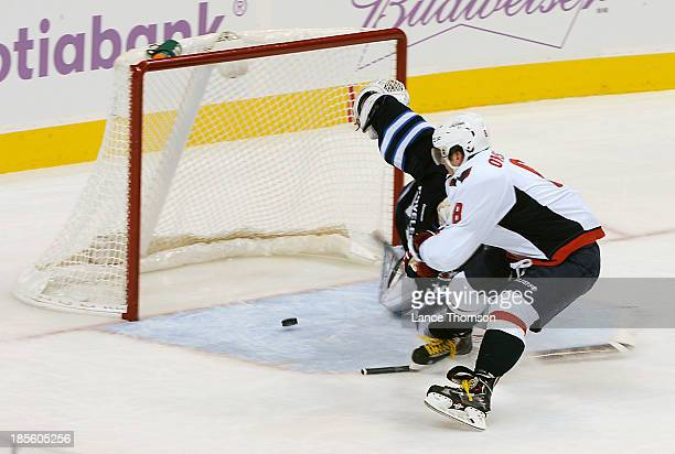 Alex Ovechkin of the Washington Capitals slides the puck in behind goaltender Ondrej Pavelec of the Winnipeg Jets during second period action at the...