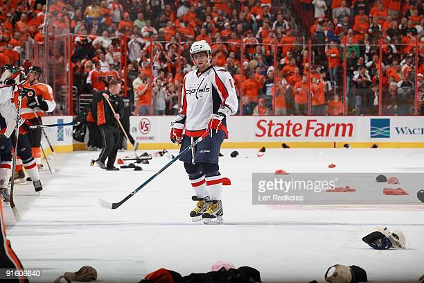 Alex Ovechkin of the Washington Capitals stands among the hat thrown onto the ice that celebrated Mike Richards's hat trick of the Philadelphia...