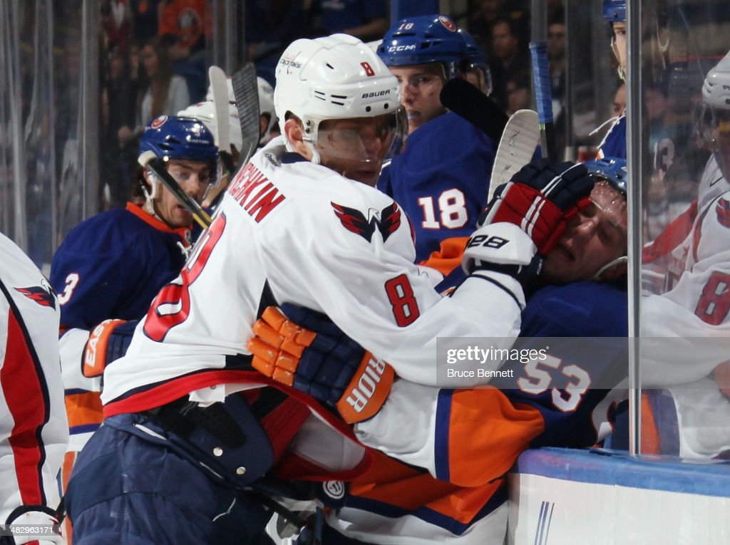 Alex Ovechkin #8 of the Washington Capitals takes a two minute roughing penalty against Casey Cizikas #53 of the New York Islanders at the Nassau Veterans Memorial Coliseum on April 5, 2014 in Uniondale, New York.