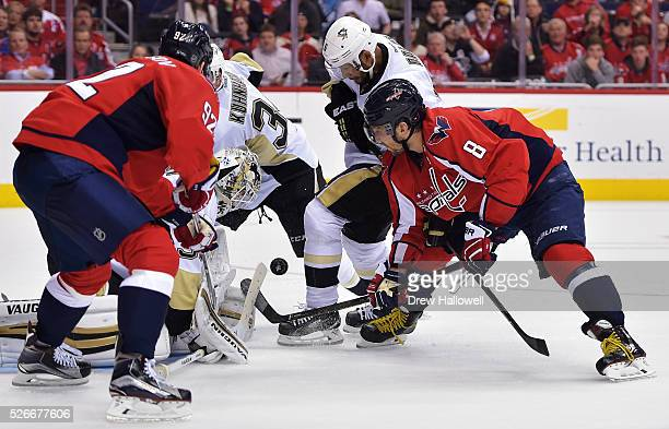 Alex Ovechkin of the Washington Capitals tries to jam the puck past Matt Murray of the Pittsburgh Penguins while fighting off Trevor Daley during...