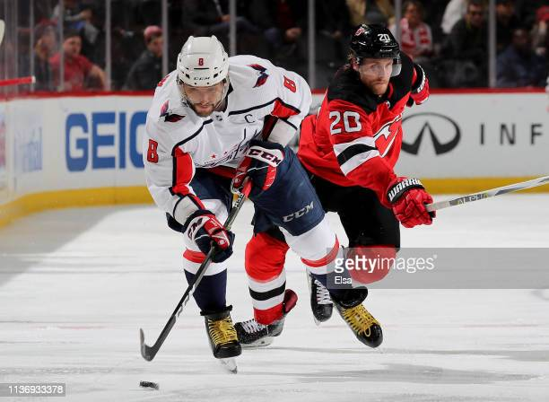 Alex Ovechkin of the Washington Capitals tries to keep the puck as Blake Coleman of the New Jersey Devils defends in the third period at Prudential...