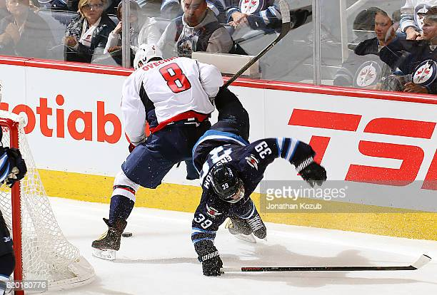 Alex Ovechkin of the Washington Capitals upends Toby Enstrom of the Winnipeg Jets behind the net during third period action at the MTS Centre on...