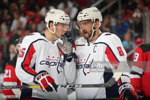 Alex Ovechkin#8 of the Washington Capitals and teammate Andre Burakovsky#65 talk during a timeout during the game against the New Jersey Devils at...