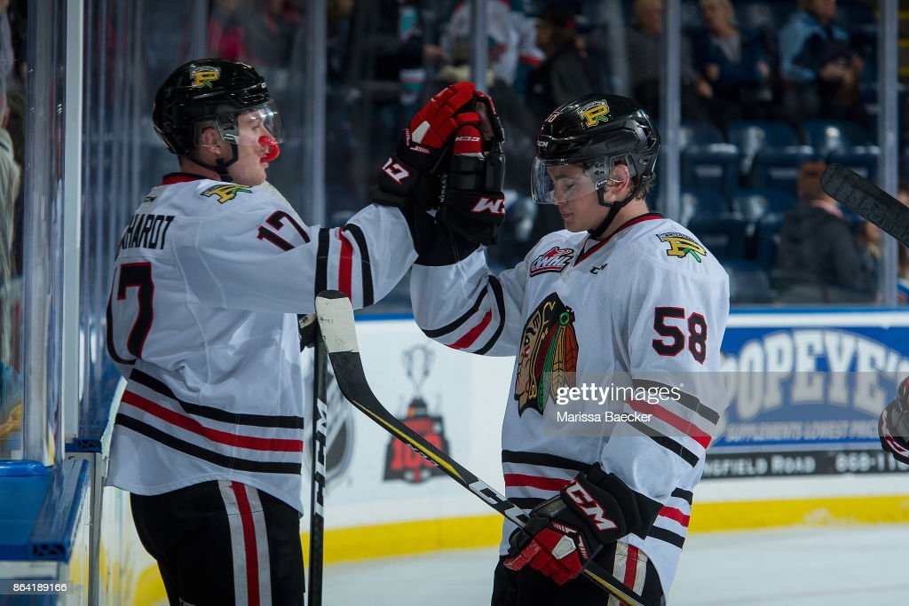 Alex Overhardt #17 high fives Clay Hanus #58 of the Portland Winterhawks and celebrates the win against the Kelowna Rockets at Prospera Place on October 20, 2017 in Kelowna, Canada.