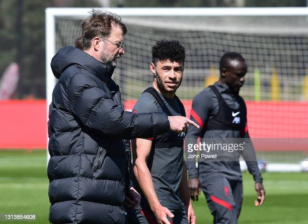 Alex Oxlade-Chamberlain and Jurgen Klopp manager of Liverpool during a training sesion at AXA Training Centre on April 22, 2021 in Kirkby, England.