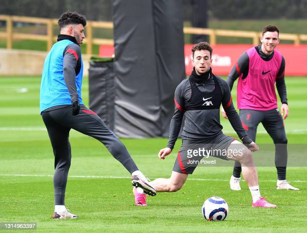 Alex Oxlade-Chamberlain and Kostas Tsimikas of Liverpool during a training session at AXA Training Centre on April 28, 2021 in Kirkby, England.