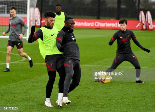 Alex Oxlade-Chamberlain and Naby Keita of Liverpool during a training session at AXA Training Centre on December 17, 2020 in Kirkby, England.