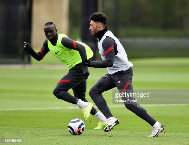 Alex Oxlade-Chamberlain and Sadio Mane of Liverpool during a training session at AXA Training Centre on May 04, 2021 in Kirkby, England.