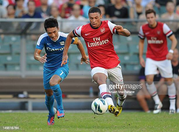 Alex Oxlade-Chamberlain of Arsenal breaks past Chu Siu Kei of Kitchee during the pre-season Asian Tour friendly match between Kitchee FC and Arsenal...