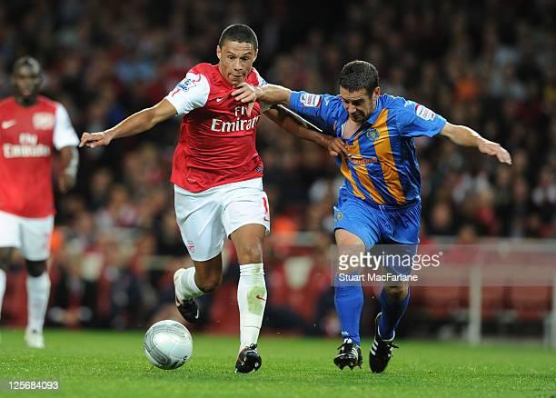 Alex OxladeChamberlain of Arsenal breaks past Sean McAllister of Shrewsbury during the Carling Cup Third Round match between Arsenal and Shrewsbury...