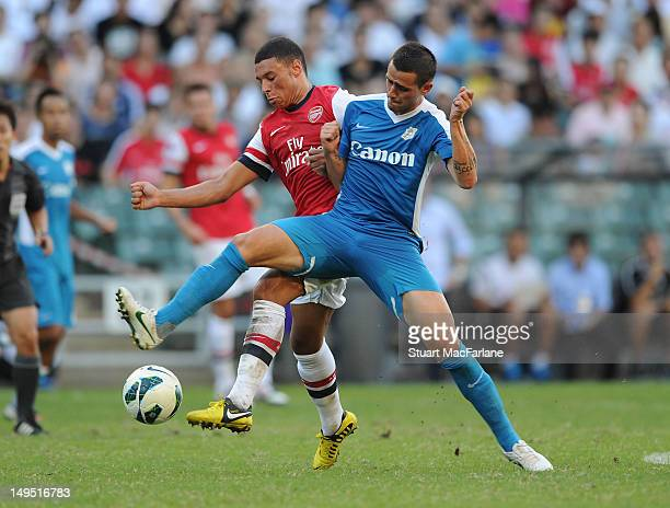 Alex Oxlade-Chamberlain of Arsenal breaks past Yago Lopez of Kitchee during the pre-season Asian Tour friendly match between Kitchee FC and Arsenal...