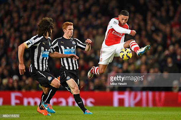 Alex Oxlade-Chamberlain of Arsenal controls the ball under pressure from Jack Colback of Newcastle United during the Barclays Premier League match...