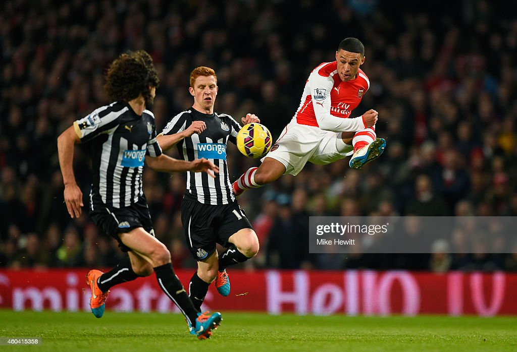 Alex Oxlade-Chamberlain of Arsenal controls the ball under pressure from Jack Colback of Newcastle United during the Barclays Premier League match between Arsenal and Newcastle United at Emirates Stadium on December 13, 2014 in London, England.