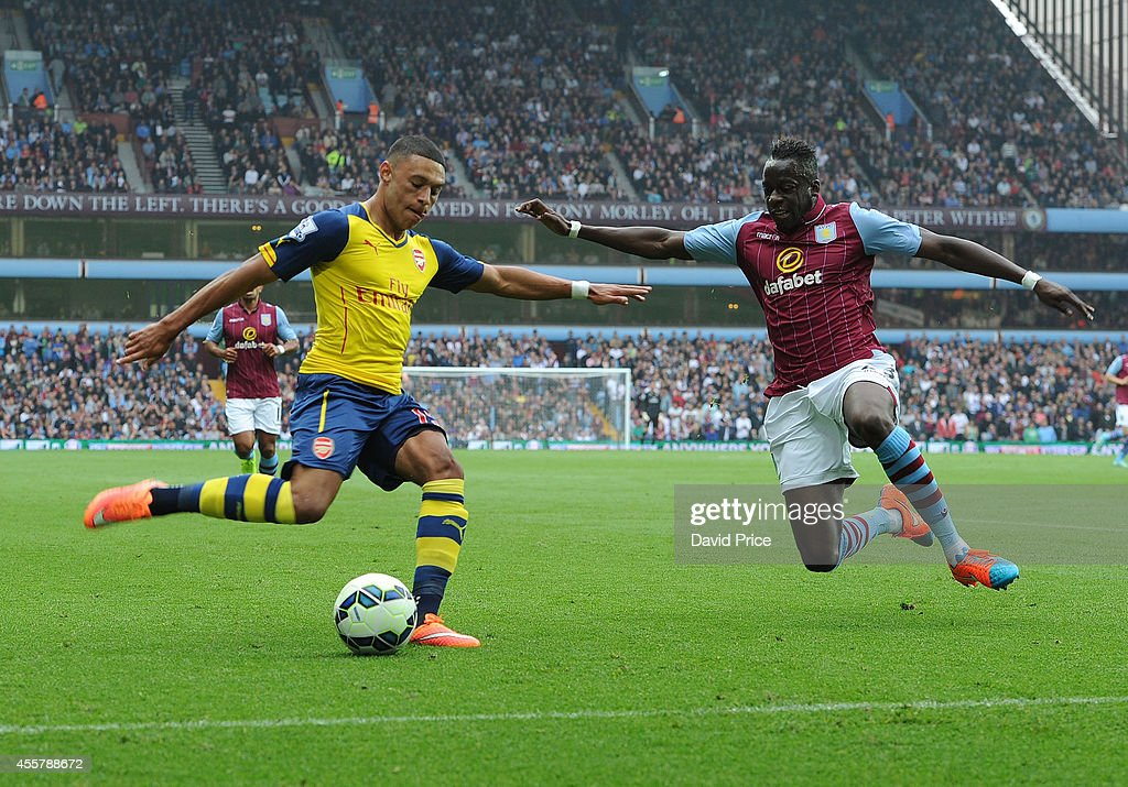 Alex Oxlade-Chamberlain of Arsenal crosses under pressure from Aly Cissokho of Villa during the Barclays Premier League match between Aston Villa and Arsenal at Villa Park on September 20, 2014 in Birmingham, England.