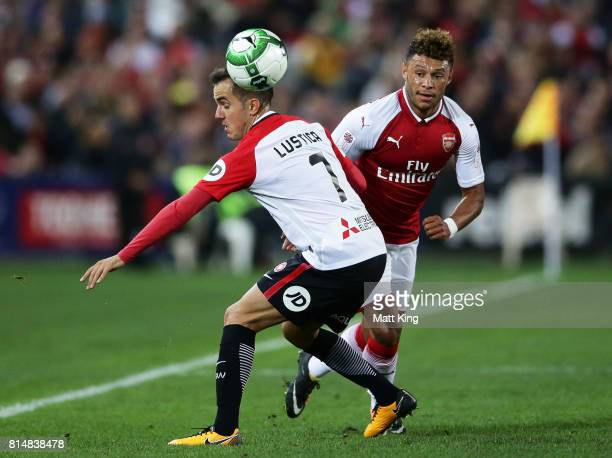 Alex OxladeChamberlain of Arsenal is challenged by Steve Lustica of the Wanderers during the match between the Western Sydney Wanderers and Arsenal...