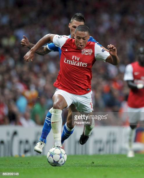Alex OxladeChamberlain of Arsenal is tracked by Jose Holebas of Olympiacos during a UEFA Champions League match at the Emirates Stadium on September...