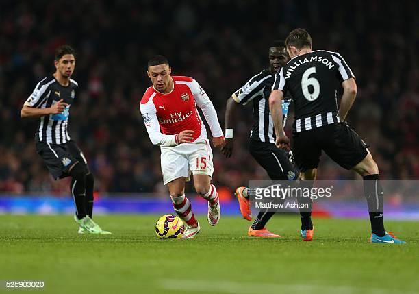 Alex OxladeChamberlain of Arsenal outruns Ayoze Perez Cheik Ismael Tiote and Michael Williamson of Newcastle United