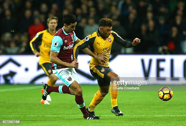 Alex OxladeChamberlain of Arsenal runs with the ball under pressure from Alvaro Arbeloa of West Ham during the Premier League match between West Ham...
