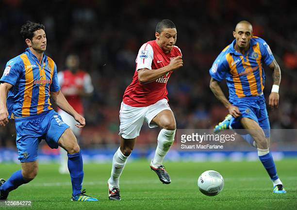 Alex OxladeChamberlain of Arsenal takes on Jermaine Grandison and Joe Jacobson of Shrewsbury during the Carling Cup Third Round match between Arsenal...
