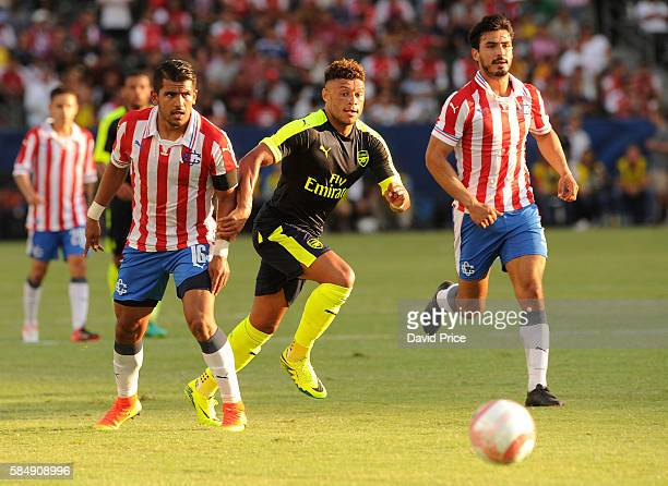 Alex Oxlade-Chamberlain of Arsenal takes on Miguel Ponce of CD Guadalajara during the match between Arsenal and CD Guadalajara at StubHub Center on...